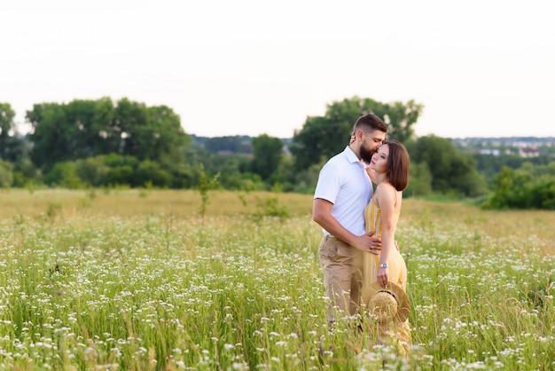 Couple amoureux câlins dans la nature parmi les fleurs sauvages en été