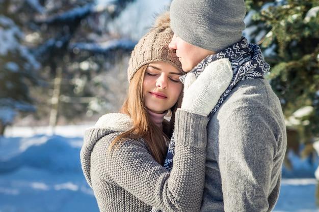 Couple amoureux câlins en forêt d'hiver