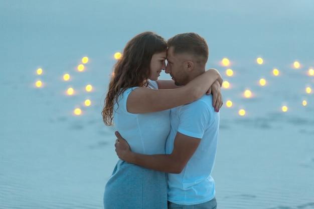 Couple amoureux calins romantiques dans le désert de sable. soirée, ambiance romantique, bougies brûlées dans le sable