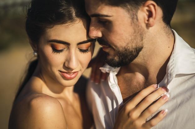 Couple d'amoureux caucasien portant des vêtements blancs et étreignant sur la plage lors d'une séance photo de mariage