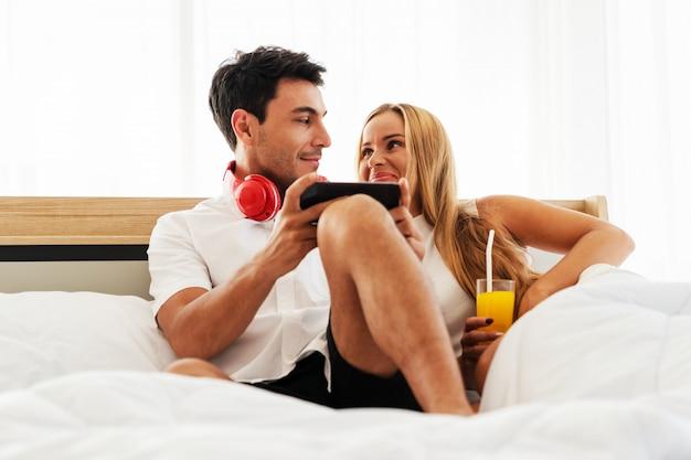 Couple amoureux caucasien s'amuser avec les médias sociaux ensemble sur smartphone ensemble dans la chambre tôt le matin