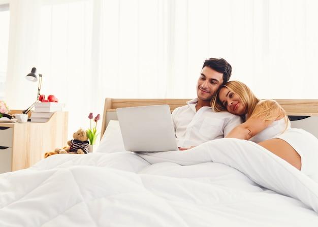 Couple amoureux caucasien souriant profiter à l'aide d'un ordinateur portable ensemble sur le lit tôt le matin