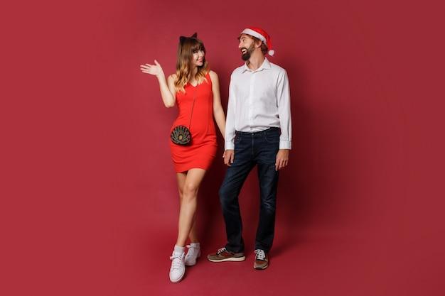 Couple amoureux en chapeaux de mascarade de nouvel an posant sur rouge. ambiance de fête.