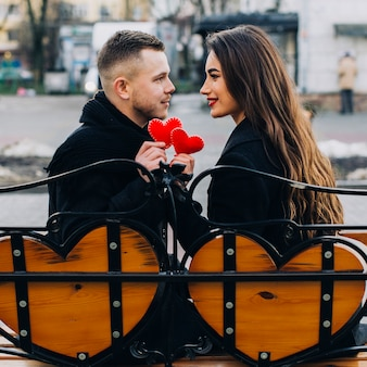 Couple d'amoureux avec des coeurs rouges sur le banc