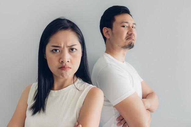 Couple amoureux en colère en t-shirt blanc et fond gris.