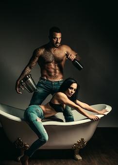 Couple amoureux de corps sexy, détendez-vous. célébration de la fête. problèmes dans les relations familiales. traiter le problème avec l'aide de l'alcool. homme musclé sexy boit du champagne de la bouteille. boisson froide avec seau à glace.
