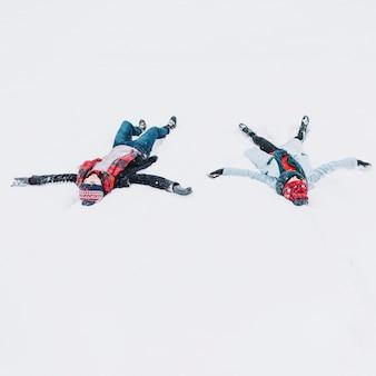 Couple d'amoureux couché dans la neige s'amuser