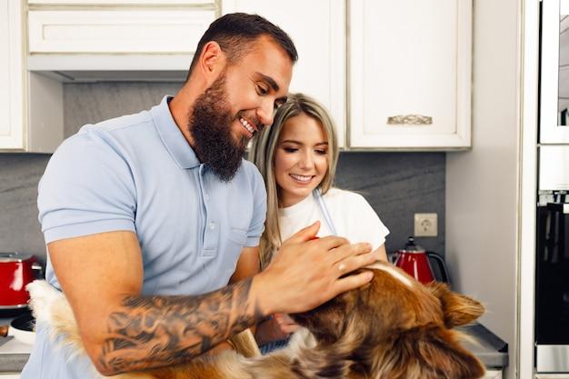 Couple d'amoureux cuisiner des aliments dans la cuisine avec leur chien border collie