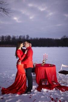 Couple d'amoureux dans de beaux vêtements rouges sur le stand de rue près de la table avec fond de neige d'hiver
