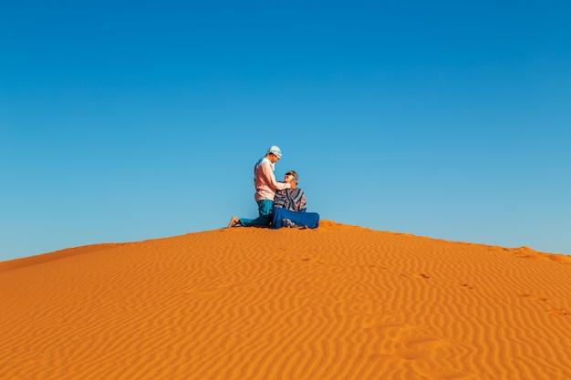 Couple d'amoureux dans le désert du sahara. repos articulaire.