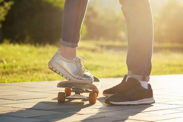 Couple amoureux dans un parc d'été. jambes pieds d'un homme et d'une femme en jeans à la mode et baskets élégantes sur un asphalte de longboard de skateboard. l'activité des jeunes et le premier concept d'amour.