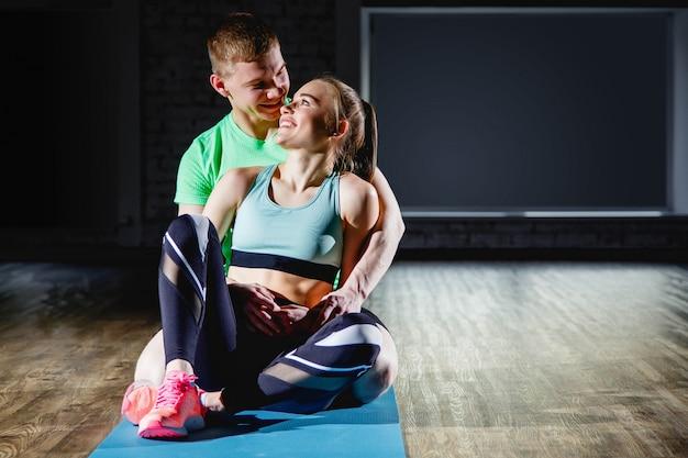 Couple amoureux dans la salle de sport se reposer après les activités sportives