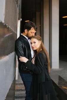 Couple amoureux dans des vêtements sombres s'embrassent.