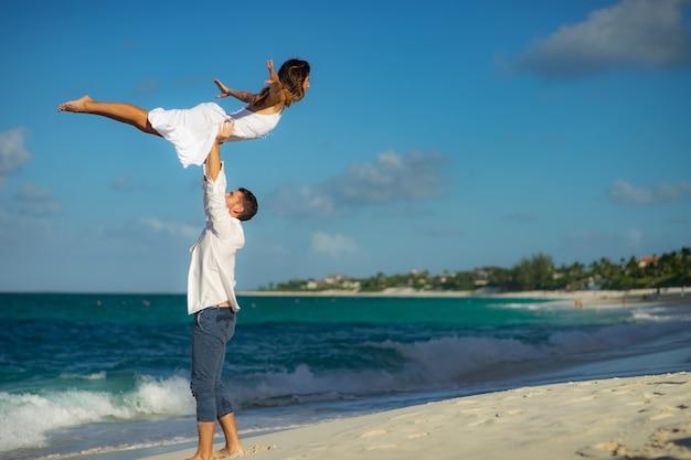 Couple d'amoureux dansant sur le sable sur la plage de la mer en été contre l'eau cristalline