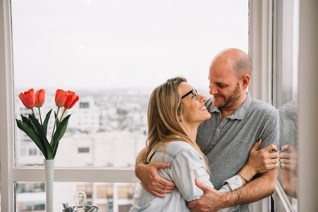 Couple amoureux devant la fenêtre