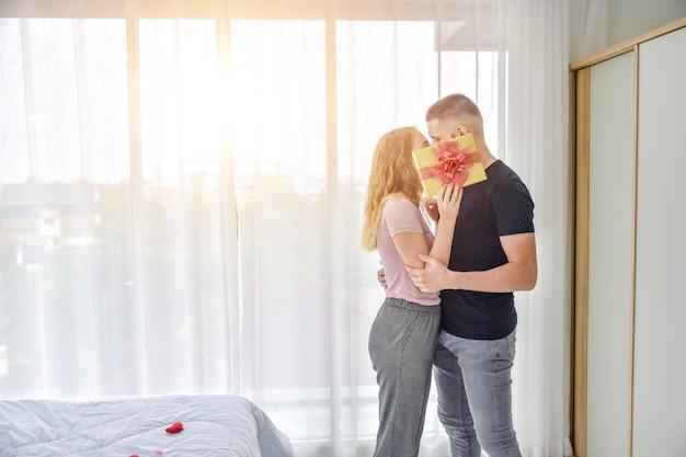 Couple amoureux donnant coffret cadeau dans le bonheur de la chambre dans le concept de la saint-valentin amour