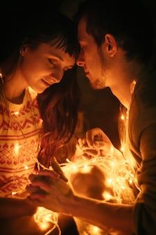 Couple amoureux embrassant la nuit avant noël