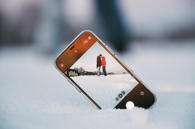 Couple d'amoureux embrassant tout en prenant selfie sur téléphone mobile placé sur la neige dans la campagne