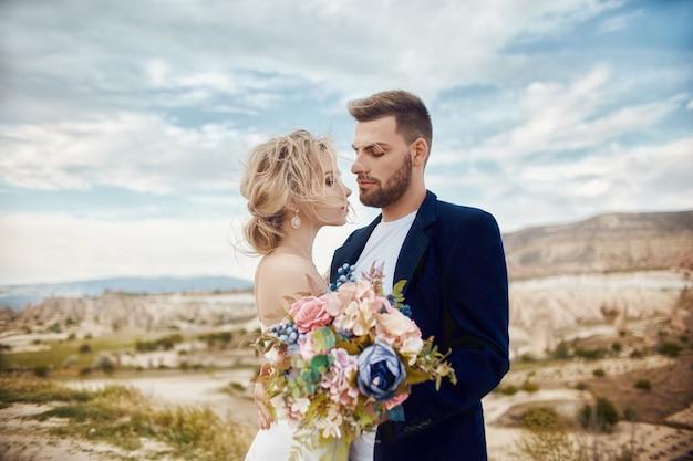 Couple amoureux embrasse et embrasse dans de fabuleuses montagnes dans la nature. femme en longue robe blanche avec bouquet de fleurs dans les mains, homme en veste. mariage dans la nature, les relations et l'amour