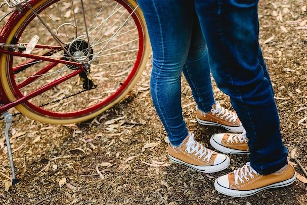 Couple d'amoureux avec des espadrilles et des jeans verts debout à côté d'un vélo vintage
