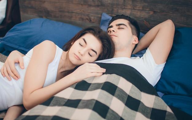 Un couple d'amoureux est allongé sur le lit. chambre lumineuse et confortable. confort et amour en famille