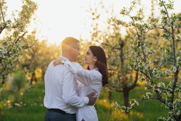Couple amoureux est étreinte à l'extérieur dans le jardin de printemps