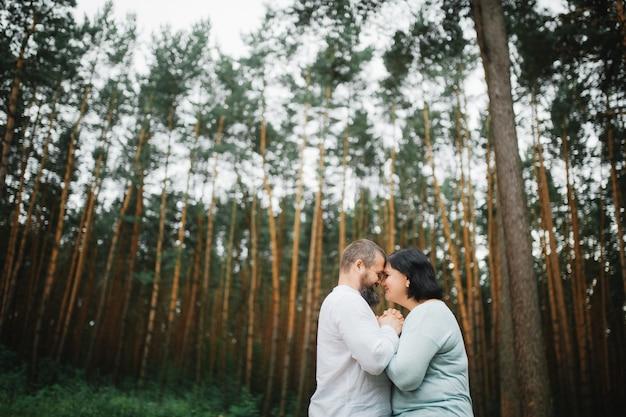Couple d'amoureux étreignant sur l'herbe verte sur la pelouse dans le parc