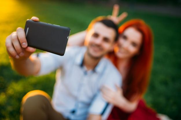 Couple amoureux fait selfie dans le parc d'été au coucher du soleil
