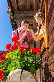 Couple amoureux à la fenêtre de la cabane de montagne