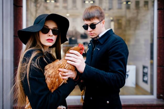 Couple amoureux glamour élégant debout contre la vitrine de la boutique. paire de hipsters à la mode en lunettes de soleil noires tenant le poulet en plein air.