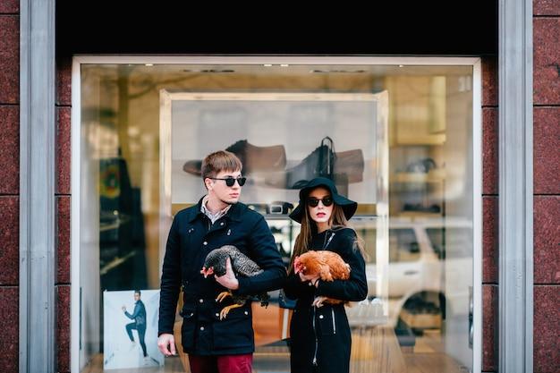 Couple amoureux glamour élégant debout contre la vitrine de la boutique. paire de hipsters à la mode en lunettes de soleil noires tenant des poulets en plein air.