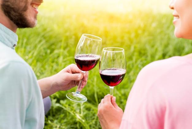 Couple amoureux grillage des verres à vin assis sur l'herbe
