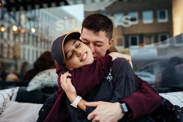 Un couple amoureux. guy et une fille se serrent dans leurs bras à une table dans un café en plein air.