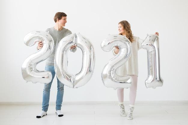 Un couple d'amoureux heureux tient des ballons en argent 2021