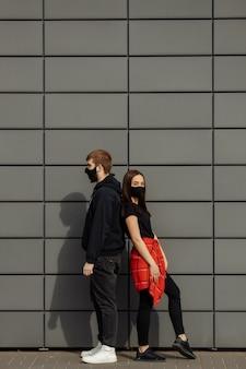 Couple amoureux, homme et femme en masque médical de protection sur le visage dans la rue