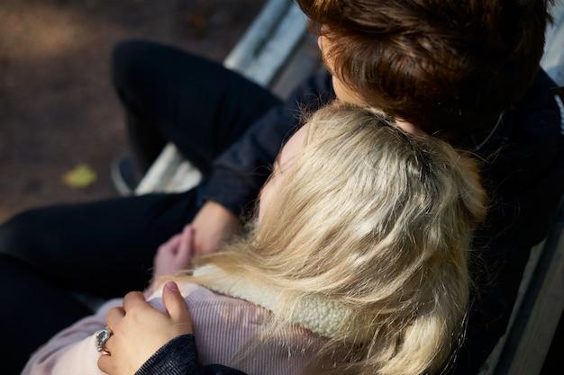 Couple d'amoureux des hommes et des femmes assis sur un banc, se reposant dans les rayons du soleil d'automne