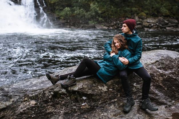 Un couple d'amoureux en imperméables verts, assis sur un rocher, dans le contexte d'une cascade
