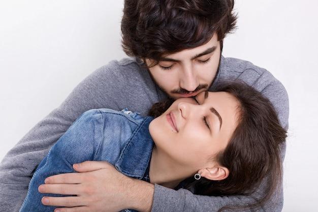 Un couple d'amoureux isolé sur mur blanc. un jeune homme embrassant et embrassant sa petite amie