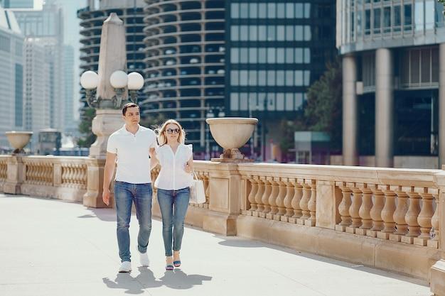 Couple amoureux jeune et élégant en t-shirts blancs et jeans marchant dans une grande ville
