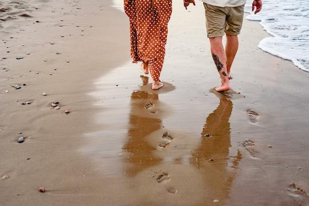Couple amoureux jouant et marchant sur le rivage de la plage.