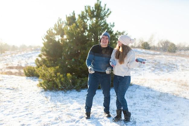 Couple d'amoureux joue aux boules de neige en hiver dans la forêt