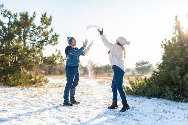 Couple d'amoureux joue des boules de neige en hiver dans la forêt