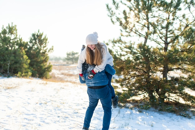 Couple d'amoureux joue en hiver dans la forêt. le gars a jeté la fille sur son dos et a couru avec elle à travers la forêt. riez et passez un bon moment.