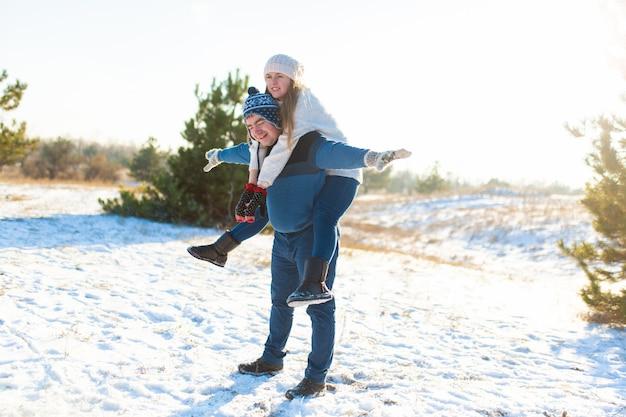 Couple d'amoureux joue en hiver dans la forêt