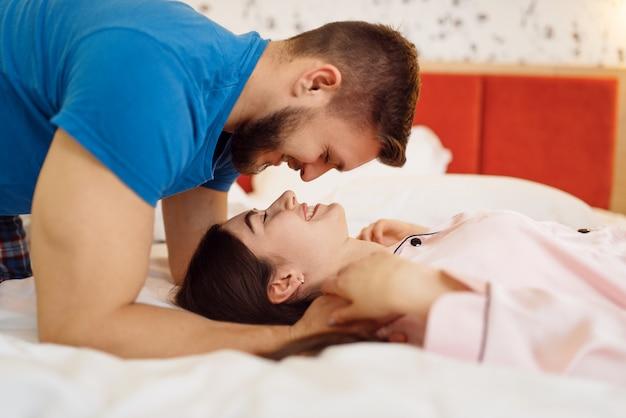 Un couple d'amoureux joyeux en pyjama s'embrasse dans la chambre à la maison, bonjour. relation harmonieuse dans la jeune famille