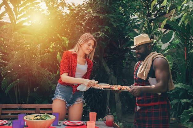 Couple amoureux lors d'une soirée barbecue en pleine nature. barbecue et fête.