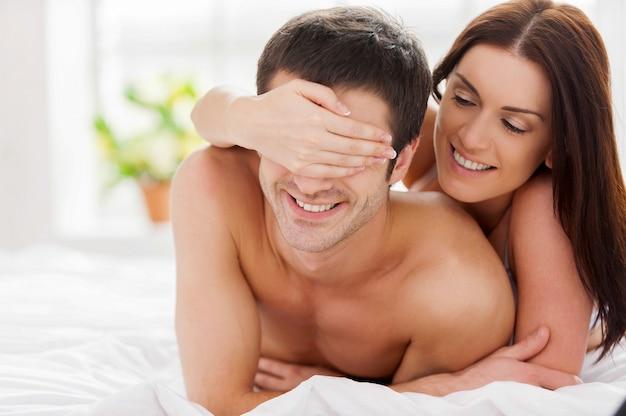 Couple d'amoureux ludique. cheerful young love couple allongé dans son lit tandis que la femme couvre les yeux de son petit ami