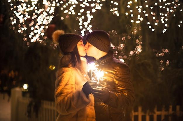 Couple d'amoureux avec une lumière du bengale étincelante s'embrassant près d'un arbre de noël