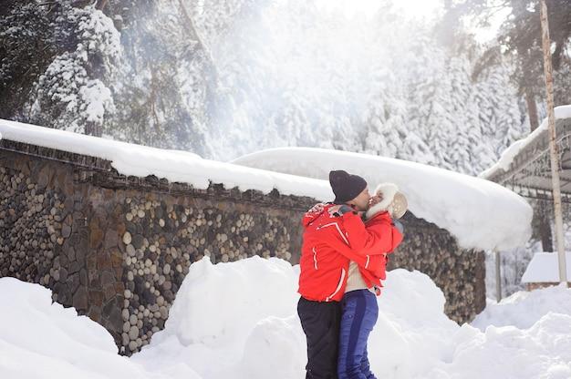 Couple amoureux main dans la main et jouant avec la neige en plein air en hiver.