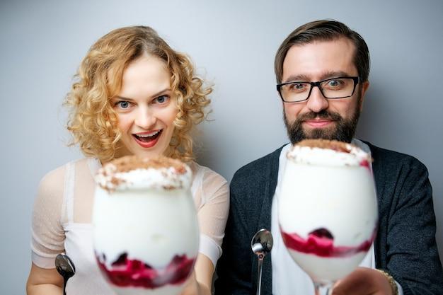 Couple d'amoureux mangeant ensemble de la crème glacée à la cerise. homme dans la fille de noeud papillon dans une robe rouge sur fond blanc